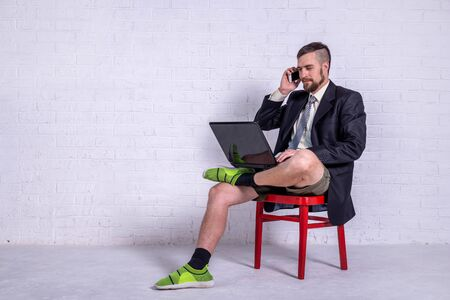 A young man in a suit and shorts works on a laptop while sitting on a chair near the wall, copy space. The concept of remote work. Freelance