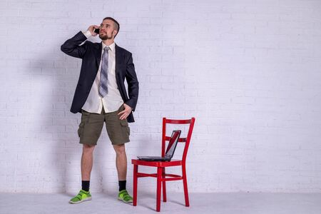 A young man in a suit and shorts is talking on the phone, and a laptop is on the chair. The concept of remote work. Freelance Standard-Bild