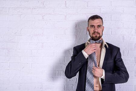 A bearded man is tying a tie. Portrait of a man. Standard-Bild