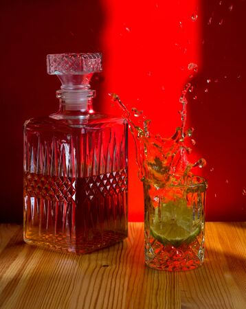 Carafe glass with a drink with lime, splashes