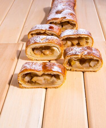 Roulade with apples, strudel sliced ??into pieces on a wooden background, close-up