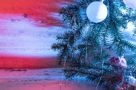 New Year's toys on fir-trees a white sphere on a light wooden background.Christmas card.Still-life