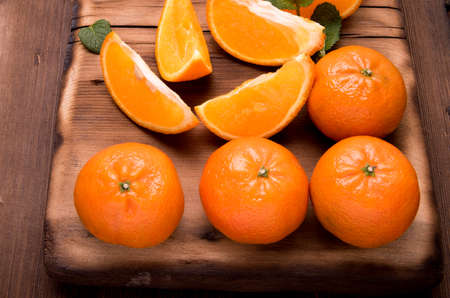 Tangerines whole slices of mint leaves on a cutting Board, an old dark wooden table, close-up with space for text Stock Photo