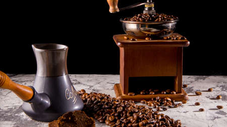 Turk old manual coffee grinder with coffee beans, close-up, space for text