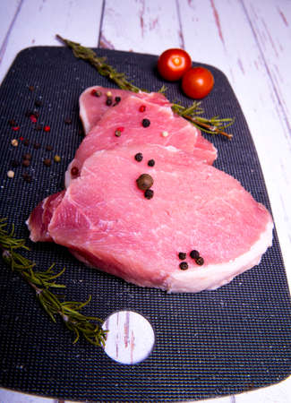 Pork. Fresh pork steaks on a black chopping board and spiced, cherry tomatoes, rosemary, peppercorns, copy space
