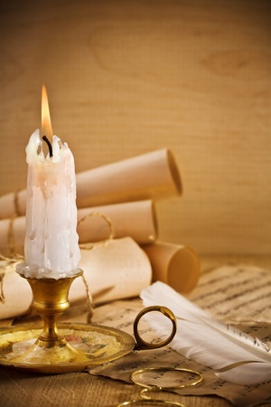 old candle on table with rolls of paper Stock Photo