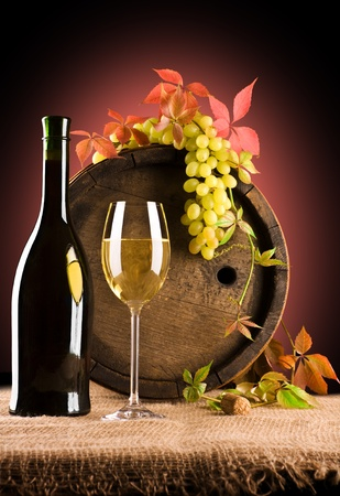 composition of white wine and grape and foliage of grape photo