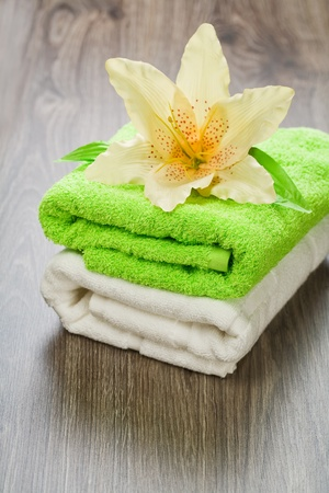 flower on towels on wooden background photo