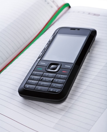 dayplanner: black mobile phone on a notepad