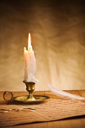 burning candle and music sheet photo