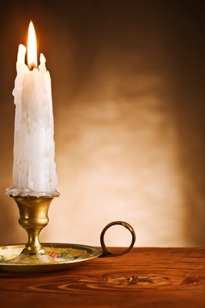 wood burning: copy space ablaze candle in old candlestick Stock Photo