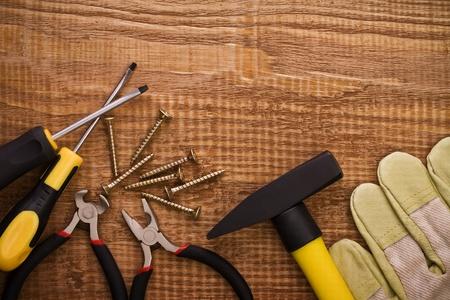 screwdriwer: hamer pliers screwdriwer and gloves on woodn board