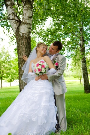The groom and the bride in park near a tree photo