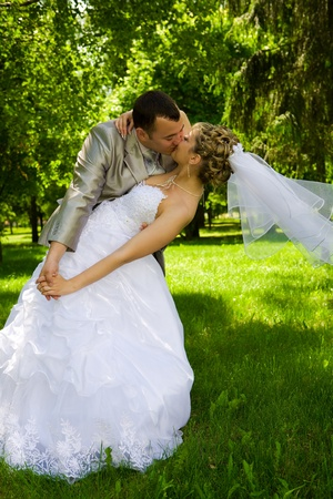 The groom holds the bride in park photo