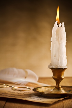 Antique brass candlestick with burning candle photo
