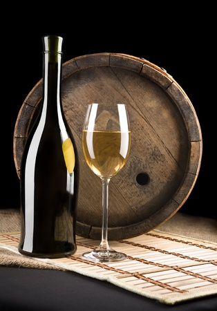 composition of white wine and bottle on a background of old wine Keg