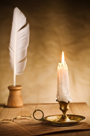 Romantic still-life with burning candle and music sheet photo