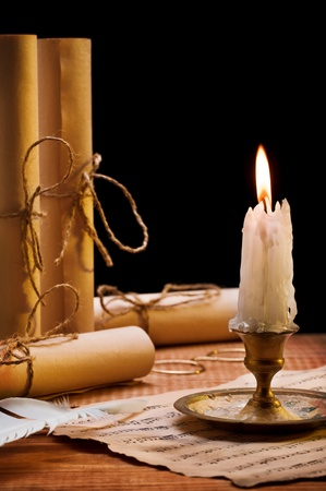 burning candle and antique items photo