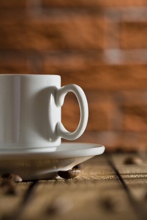 white coffee cup on a background of a brick wall Stock Photo - 13029082