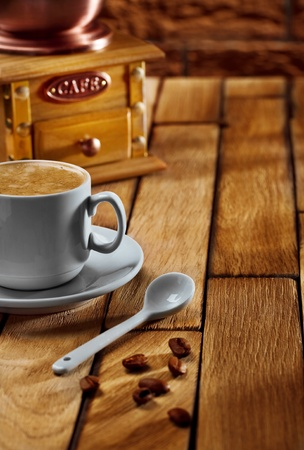close-up coffee cup and grinder on wooden table photo