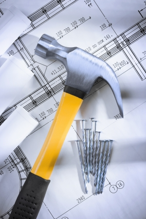 claw hammer and nails with blueprints photo