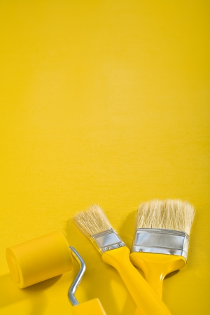 paintroller: copyspace image Brushes and paint-roller on a yellow background Stock Photo