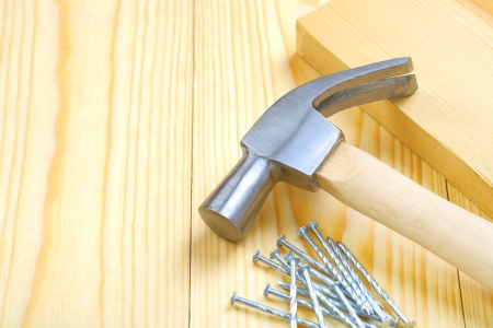hammer with nails and plank photo