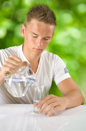 boy filling water in the glass Stock Photo