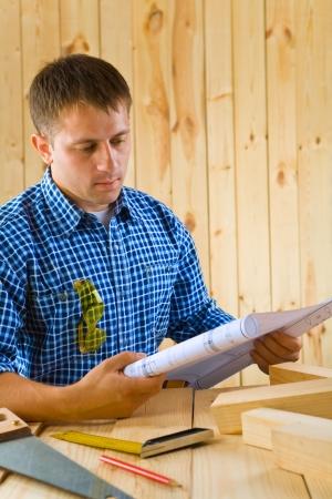 carpenter looks on the blueprint photo