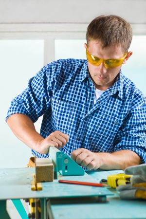 worker adjusts the woodworking mashine photo