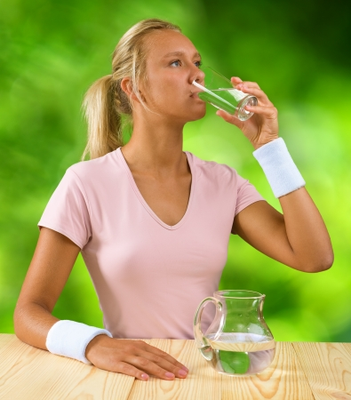 a girl drinking water from glass photo