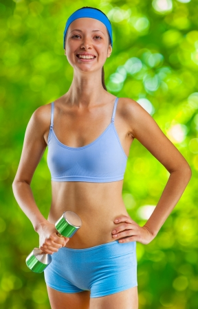 girl in sportswear: buoyant girl with dumbbell Stock Photo