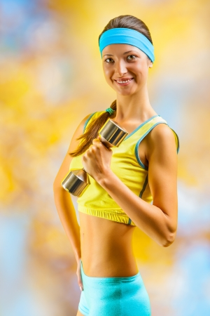 a beautyful sporty girl with dumbbell photo