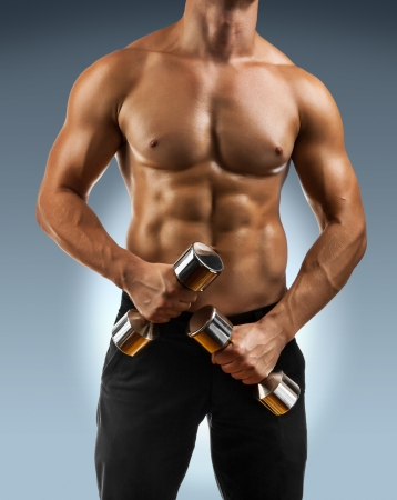 a muscular male torso with dumbbells Stock Photo