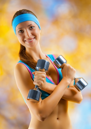 a sports girl with two dumbbells photo