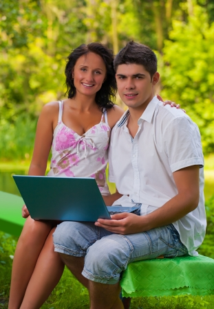 couple sitting with laptop in park photo