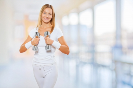 a female wearing sports clothes holding barbells photo