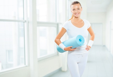 a female wearing white sports clothes holding blue yoga mat photo