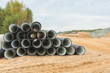 stack of big pipes on construction place photo