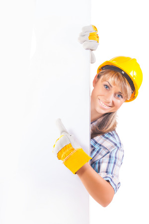 Female construction worker with blank board isolated on white photo