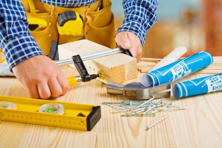 carpenter vise: hands of carpenter do fixing of wooden planks