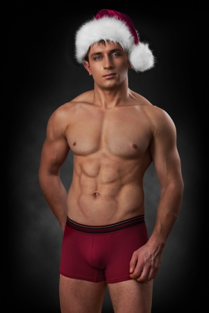 muscular man in red santa cap on dark background photo