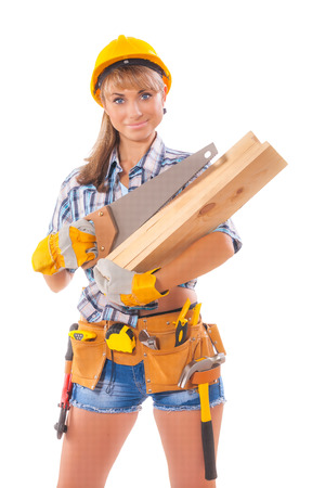 Halfl length portrait of happy female construction worker with handsaw and wooden planksl and tool belt standing isolated over white background photo