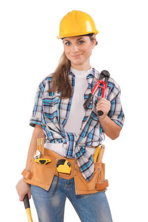 construction work: beautiful sexy girl in work wear holding tools isolated on white background