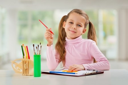 a young girl with pencil sitting at table photo