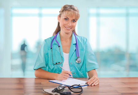 beautiful female doctor sitting at table and writing in clipboard photo