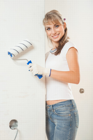paintroller: beautiful female painter near the wall  holding paintroller Stock Photo