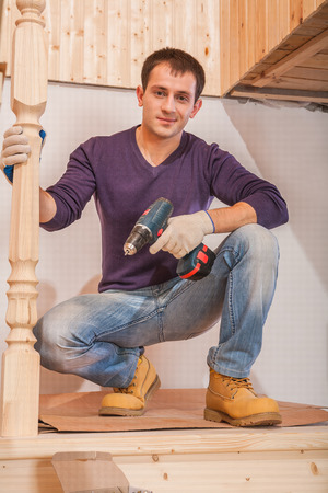 a young carpenter sitting and holding cordless drill photo