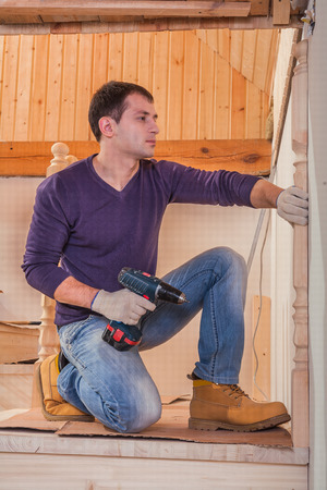 worker sitting and holding cordless drill photo