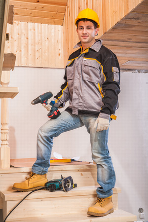 contractor standing on ladder and holding cordless drill photo